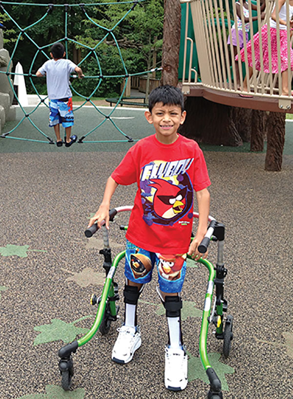 AFOs and a walker allow this child to cover long distances on the playground and in the community. (Photo courtesy of Robyn Winston Cohen, CTRS.)